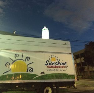 Sunshine Dairy truck in front of the building with giant milk carton on top